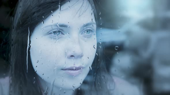 Thumbnail for Thoughtful Young Woman Looking Through Rain Window Thinking About Life