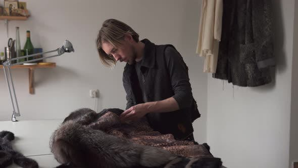 Cover Image for Man Tailor Touching Fur for Sewing Coat in Furrier Workshop