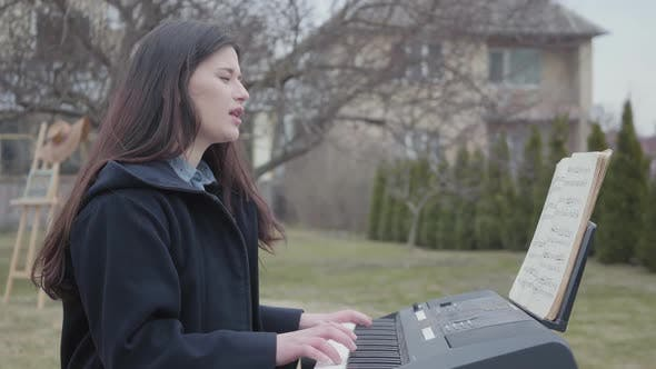 Thumbnail for A Successful Beautiful Brunette Girl Plays on a Synthesizer and Sings While Sitting in the Backyard