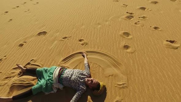 Thumbnail for Beautiful woman making sand angel in desert, Egypt