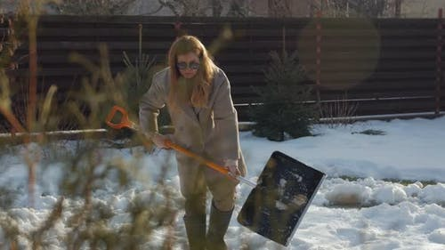 Young Woman Shoveling Snow