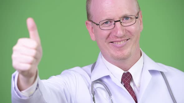 Happy Mature Bald Man Doctor Giving Thumbs Up