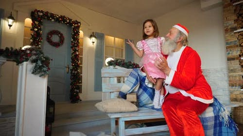 Grandfather Playing Santa Claus Role for Granddaughter.