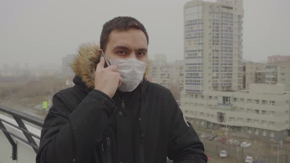 Thumbnail for Man in a Medical Mask Speaks Seriously on the Phone Cityscape in the Background