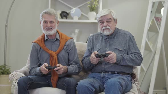 Thumbnail for Portrait of Two Cheerful Caucasian Old Men Playing Video Game. Happy Grey-haired Retirees Having Fun