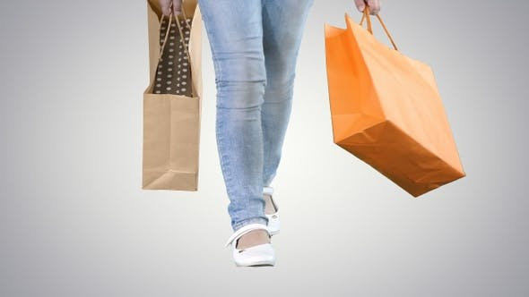 Thumbnail for Little girl with shopping bags walking on gradient background.