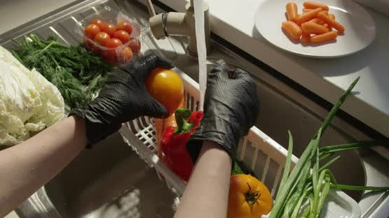 Washing Vegetables In A Sink A Slow Motion Shot With Woman In Black Gloves And Water