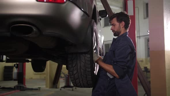 Thumbnail for Skillful Auto Mechanic Putting Wheel on Raised Car