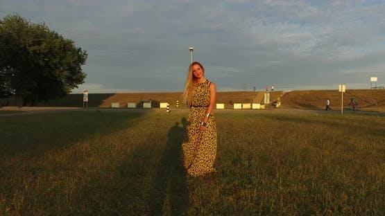Beautiful women walking barefoot in grass at sunset
