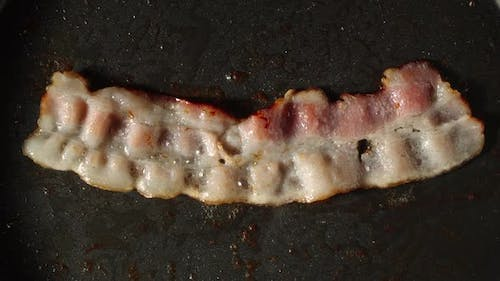 Close Shot Of Bacon Frying On A Pan