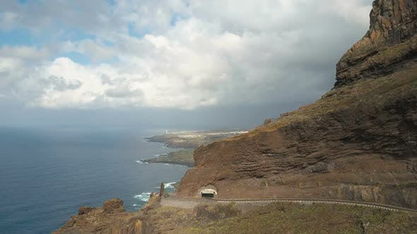 Thumbnail for Aerial View of Steep Cliffs Over Atlantic Ocean. Mountain Road and Tunnel in a Rock. Flight Toward
