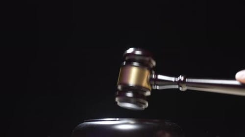 A Judge is Hitting Gavel Off a Block in Courtroom
