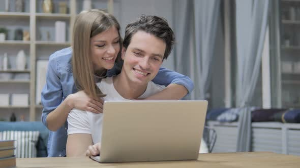 Cover Image for Happy Young Couple Selecting Things To Buy Online, Using Laptop