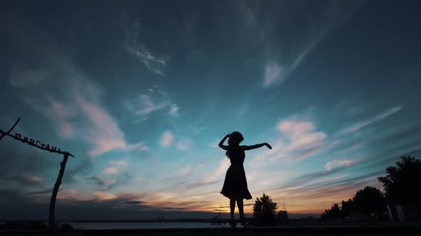 Thumbnail for Silhouette of a Ballerina Dancing Against the Sunset Sky. Girl Dancing and Spinning on Tiptoe