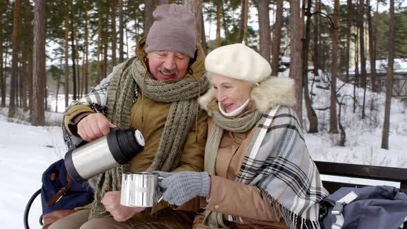 Thumbnail for Lächelnd Senior Paar Trinken Heißer Tee im Freien im Winter