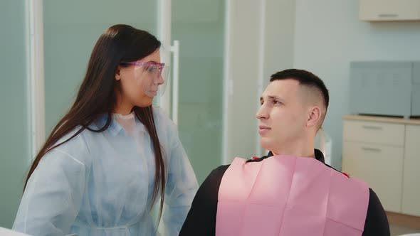 Caucasian Female Doctor and Male Patient at Doctor's Office