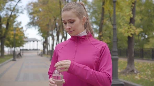 Thumbnail for Porträt einer jungen kaukasischen Frau in rosa Sportbekleidung nähert sich der Kamera, Trinkwasser