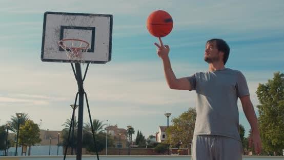 Thumbnail for Basketball Ball Balancing und Spinning auf einem Finger Spieler auf einem Outdoor-Basketballplatz
