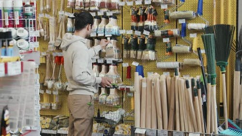 Slowmo of Man Shopping for Paintbrush and Paint Roller at Store