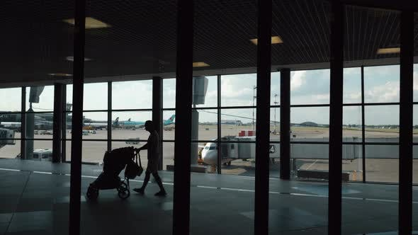 Thumbnail for People Walking in the Terminal Overlooking Boarding Plane
