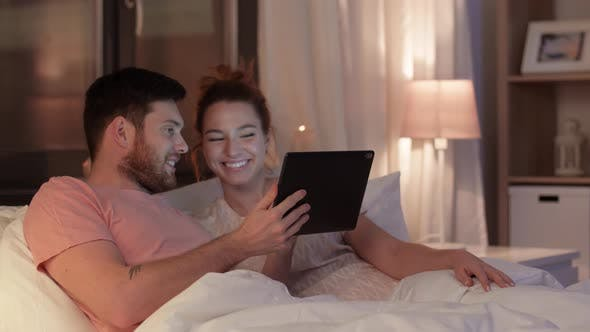 Thumbnail for Happy Couple Using Tablet Computer in Bed at Night 23