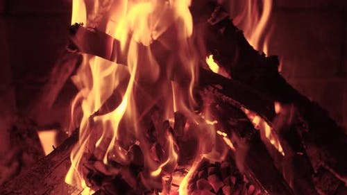 Wood Burning Slowly with Orange Fire Flame in Cozy Brickwork Fireplace Atmosphere.