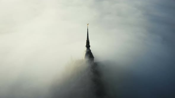 Thumbnail for Amazing Aerial Shot of Thick Fog Covering Majestic Mont Saint Michel Fortress Castle Spire at