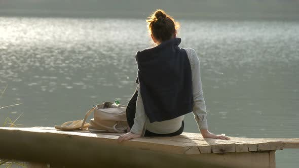 Thumbnail for Woman sitting on a wooden dock near a lake