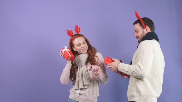 Glückliches junges Paar in weißen Pullovern, das vor Glück mit Weihnachtsgeschenken in den Händen tanzt.
