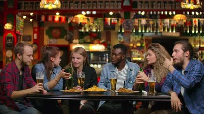 African American with Friends at a Bar Drinking Beer and Eating Chips with Friends