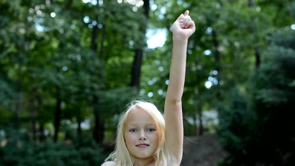Thumbnail for Little Lively Girl Puts Hand Up and Shake It in the Park