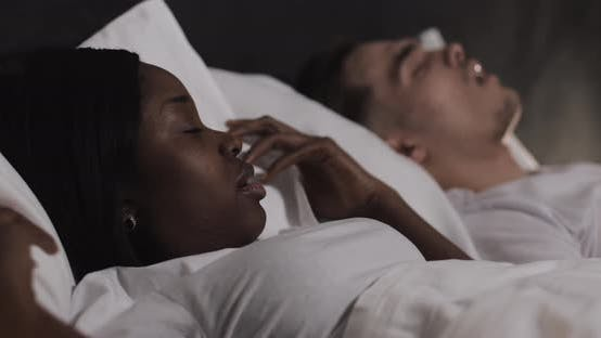 Thumbnail for Multi-ethnic Couple Lying in Bed Together. Woman Suffers From Her Partner Snoring in Bed.