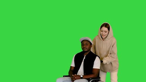 Disabled African American in a Wheelchair Waiting for His Caucasian Girlfriend on a Green Screen