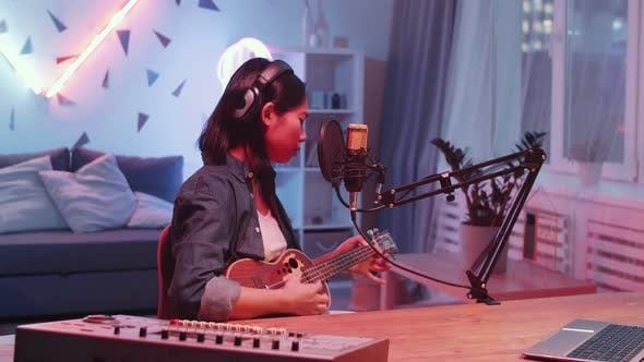 Thumbnail for Asian Woman Playing Guitar and Recording Song in Home Studio
