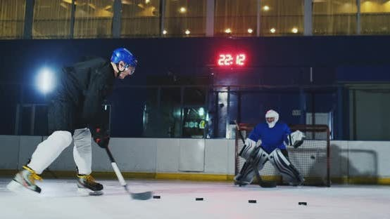 Thumbnail for Professional Hockey Player and Goalkeeper Train Punching Puck on Goal. Goalkeeper and Player in