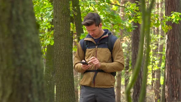 Thumbnail for A Backpacker Works on a Smartphone in a Forest, Then Walks Off