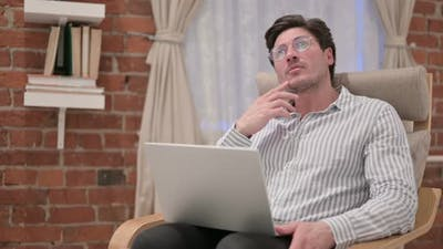 Middle Aged Man with Laptop Thinking on Sofa