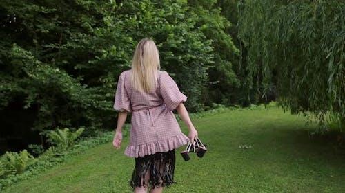 Fashion woman holding shoes in hand walking on grass through green public garden