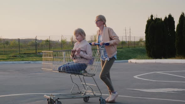 Thumbnail for Woman Having Fun in the Parking Lot at the Supermarket, Rolls the Child in the Shopping Trolley