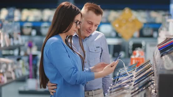 Couple Looking for New Smart Phone To Buy. Technology Shopping Concept.