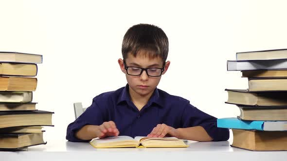 Boy Sits at the Table Leafing Through the Pages of a Book. White Background.