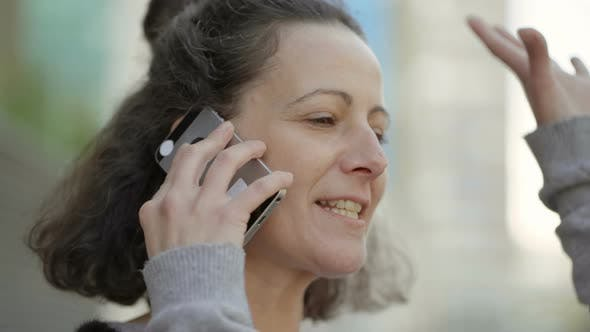 Thumbnail for Smiling Mature Brunette Talking on Smartphone Outdoor