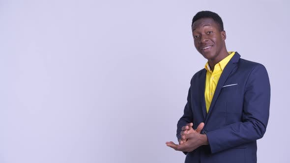Young Happy African Businessman Presenting Something To the Side