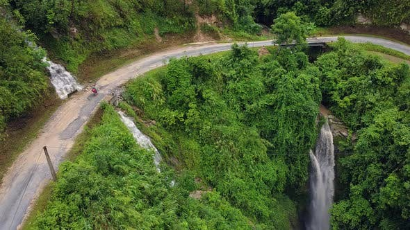 Thumbnail for A Motorbike Traveler Driving on the Small Road with Waterfalls and Greenery.