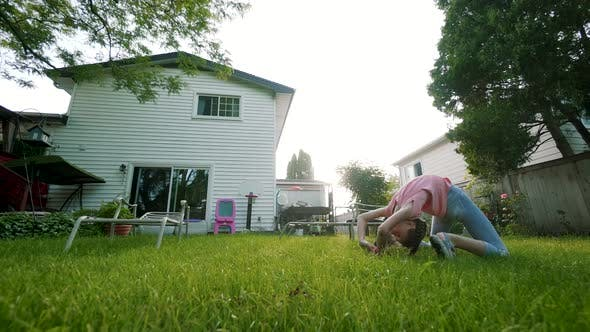 The Child Is Engaged in Acrobatics at Sunset in Back Yard. Play Game. Slow Motion