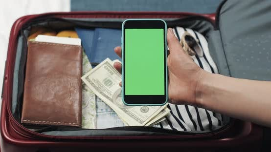 Cover Image for Young Woman Getting Ready for a Trip. She Holding Smartphone with Green Screen on the Suitcase