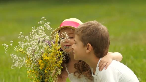Thumbnail for Children Sit on the Lawn in the Park and Sniff Freshly Harvested Field Flowers. Slow Motion