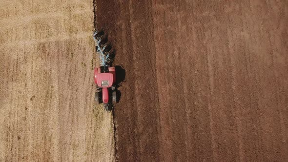Thumbnail for a Redder Tractor Plows a Field