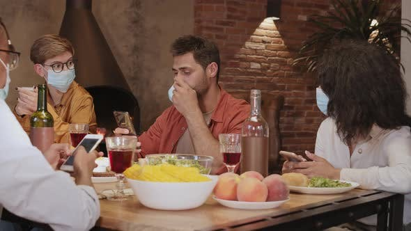 Thumbnail for Multiethnic People in Masks Using Smartphones during Dinner