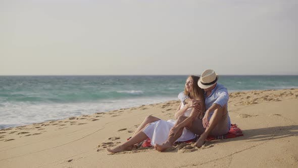 Thumbnail for Couple Sitting on Plaid at Sandy Beach